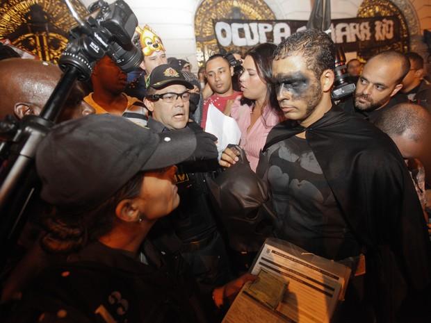Batman mascarado mostra a cara e documento em manifestação no Centro do Rio (Foto: Bruno Poppe /  Estadão Conteúdo)