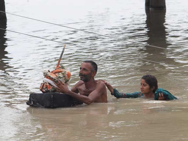 Casal deixa região de Rajanpur (Foto: Asim Tanveer / AP Photo)