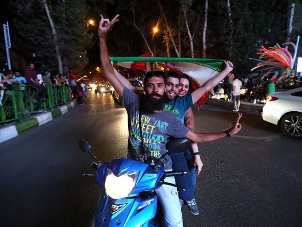 Iranianos comemoram na rua o acordo do Irã com potências ocidentais sobre o programa nuclear do país (Foto: AFP PHOTO/ATTA KENARE)