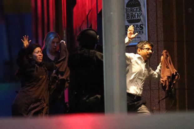 Reféns são vistos deixando local de sequestro na Austrália pouco antes de a polícia invadir o local (Foto: Rob Griffith/AP)