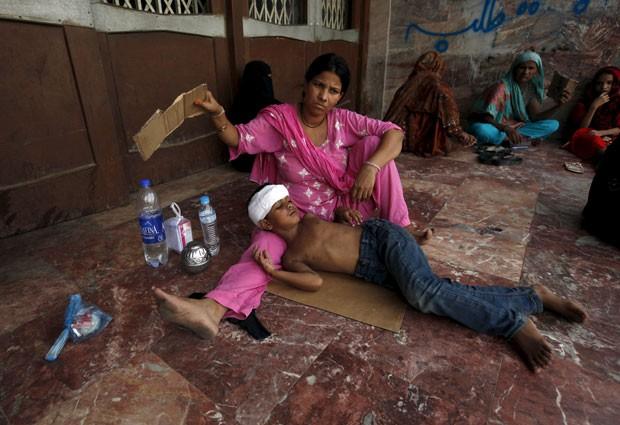 Mulher abana filho do lado de fora de hospital em Karachi, no Paquistão, nesta terça-feira (23), em meio a onda de calor que já matou centenas de pessoas no país (Foto: Akhtar Soomro/Reuters)