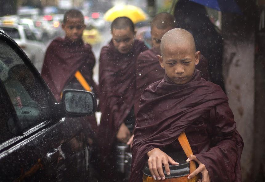 Monges budistas novatos recebem ofertas em Yangon, Myanmar, seguindo os costumes religiosos de não usar sapatos ou guarda-chuva