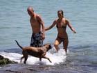 Alice Dellal passeia em praia do Rio com namorado e cachorro