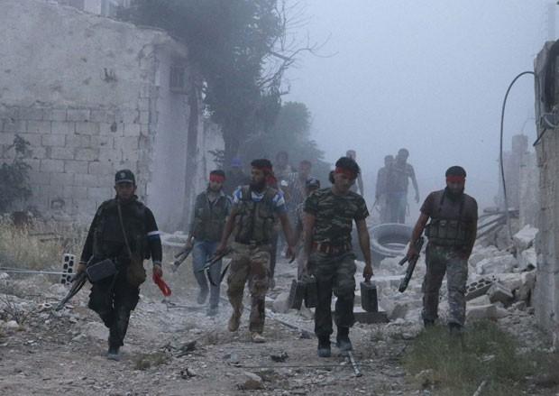 Rebeldes deixam local de explosão que teria matado 30 combatentes do governo sírio nesta terça-feira (6) (Foto: Rasem Ghareeb/Reuters)