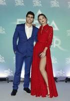 Juliana Paiva esconde fenda com bolsa e beija Juliano Laham em festa