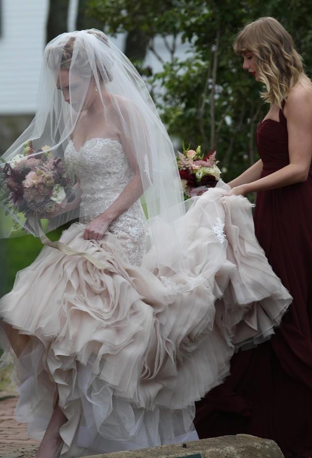 Taylor Swift  segura cauda de vestido de amiga noiva (Foto: BackGrid)