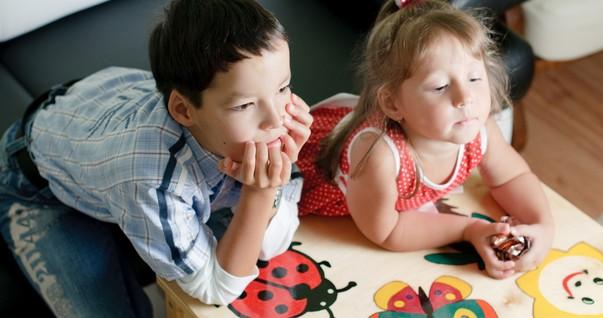 Crianças apoiadas na mesa assistindo televisão (Foto: Shutterstock)