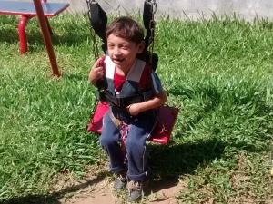 Com o colete, menino fica preso com segurança (Foto: Escola Vivendo a Infância/Divulgação)