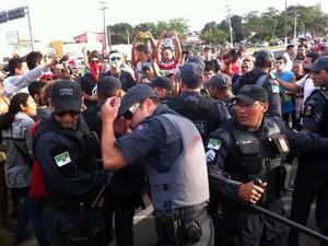 Policiais militares se protegem de pedras atiradas por manifestantes durante protesto na inauguração da Arena das Dunas, em Natal (Foto: Felipe Gibson/G1)