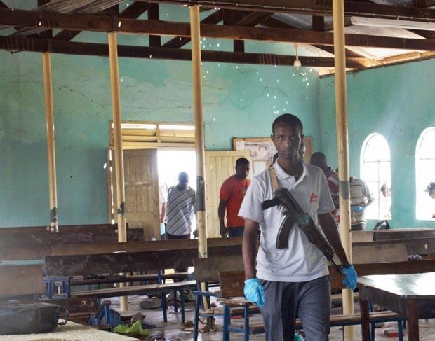 Polícia armado caminha em igreja atacada em Garissa. (Foto: Chris Mann/AP)