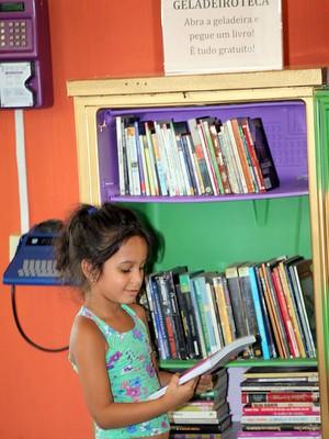 Garota pega livro em geladeiroteca no Centro de Limeira (Foto: Divulgação/Prefeitura de Limeira)