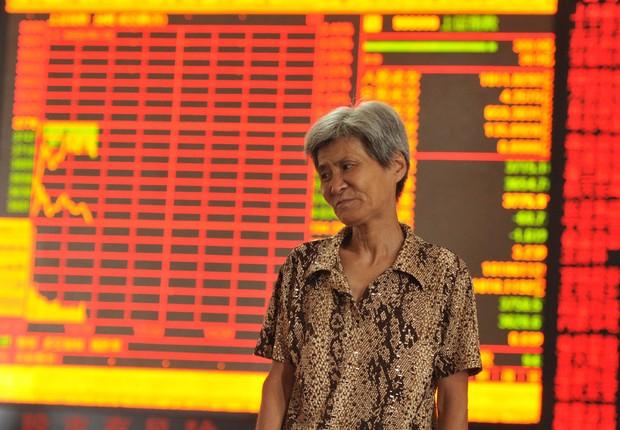 Investidora observa queda nas ações na Bolsa de Xangai e em outras bolsas de valores asiáticas em centro de Fuyang, na província de Anhui, China (Foto: ChinaFotoPress/ChinaFotoPress via Getty Images)