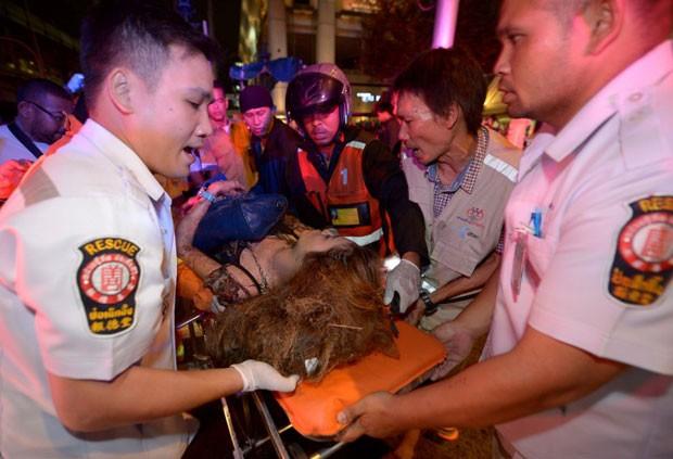 Equipe de resgate atende feridos no local onde explodiu uma bomba no centro de Bangcoc (Foto: Pornchai Kittiwongsakul / AFP)