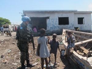 Militar brasileiro brinca com crianças em Cité Soleil (Foto: Tahiane Stochero/G1)