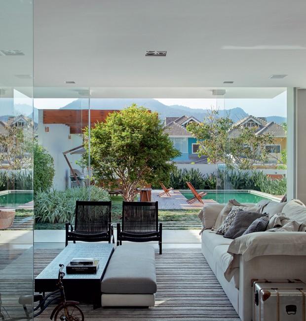 Home theater | Com vista para o jardim e a piscina, o espaço tem sofá e pufe de linho Vivence Interiores, e poltronas de corda da Galeria 021. Triciclo da By Floor (Foto: MCA Estúdio)