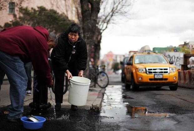 Moradores de Nova York tentam recolher água de hidrante em meio aos estragos causados pela supertempestade Sandy (Foto: AFP)