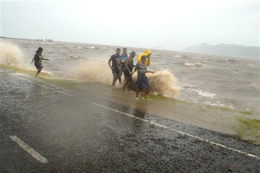 Moradores de Labasa fogem das ondas na ressaca trazida pelo ciclone  (Foto: Luke Rawalai/Fiji Times via AP)