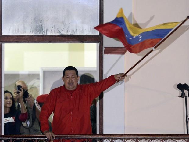 O presidente da Venezuela, Hugo Chávez, celebra sua vitória na noite de domingo (7) em sacada do Palácio de Miraflores, em Caracas. Ele teve 54,42% dos votos (7.444.082), contra 44,97% (6.151.544) do oponente, com mais de 90% dos votos apurados. (Foto: Juan Barreto/AFP)