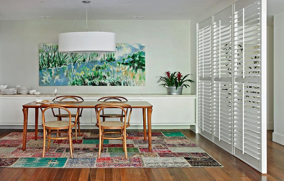Como a sala de jantar ficava logo na entrada da casa da apresentadora Patricya Travassos, a designer de interiores Paola Ribeiro instalou uma brise para criar o corredor. O ambiente ficou colorido e calmo com o quadro e o tapete de patchwork