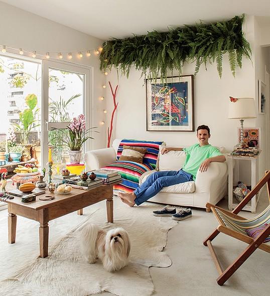 O apartamento do diretor de arte de cinema Thiago Bastos é em São Paulo, mas cheio de referências de Salvador e do Rio de Janeiro. Sobre a porta da varanda, um fio de luz dá o tom divertido à sua sala de estar