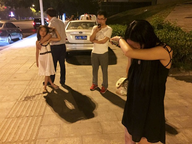 Pessoas na cidade chinesa Tianjin choram em rua próxima à explosão (Foto: REUTERS/Stringer)