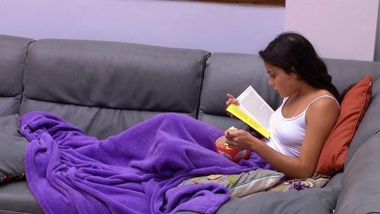 Emilly lê livro no sofá da sala