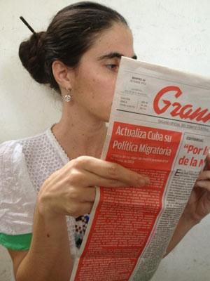 Foto posta por Yoaní Sanchéz no Twitter mostra a blogueira cruzando os dedos enquanto lê jornal oficial 'Granma' com a notícia sobre a nova lei migratória (Foto: Reprodução)