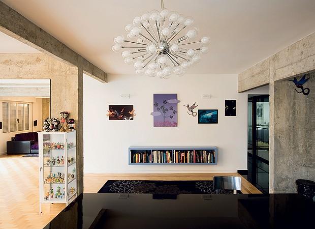 Com tudo integrado, da sala de jantar dá para ver o hall (à dir.) e o corredor para a suíte, com piso de porcelanato. Lustre da Decorlight. Os livros ficam no móvel de madeira suspenso da área de circulação e a coleção de toy art, no armário de ferro tipo (Foto: Maíra Acayaba)