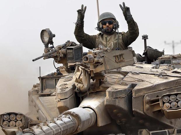 Um soldado israelense faz sinal de vitória a bordo de seu tanque perto da fronteira entre Israel e a Faixa de Gaza (Foto: Thomas Coex/AFP)