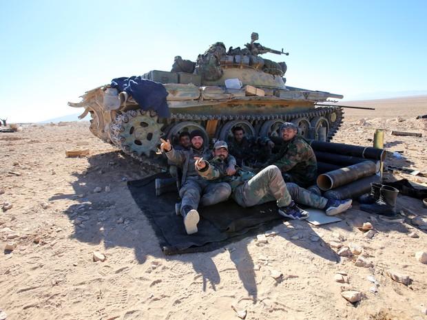 Forças do governo sírio descansam perto de tanque em Mahin, perto da cidade cristã de Sadad (Foto: Youssef Karwashan/AFP)