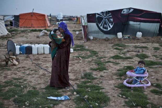 Foto de 8 de março mostra a refugiada síria Rifaa Ahmad, de 50 anos, com sua neta em um assentamento informal perto da fronteira da Síria com a Jordânia (Foto: Muhammed Muheisen/AP)