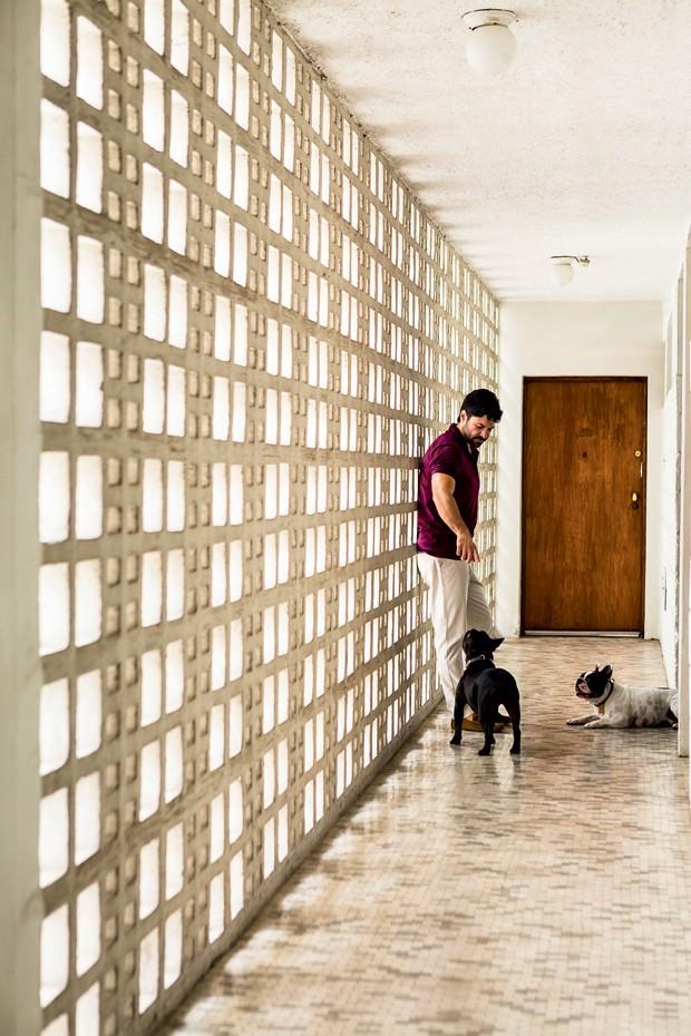 Maximiliano brinca com seus buldogues Ernesto e Ignácio, recostado em cobogós no corredor do prédio dos anos 1950 (Foto: Edu Castello/Editora Globo)