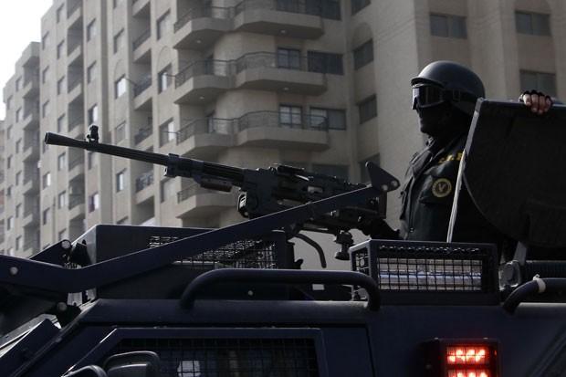 Membro das forças de segurança do governo egípcio patrulha subúrbio do Cairo durante protesto (Foto: Ahmed Abdel Fattah/AP)