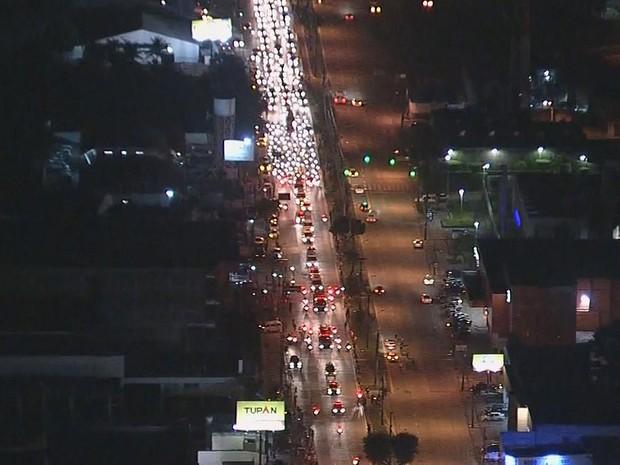 Veículo do Corpo de Bombeiros segue a 20km/h, em média, e longa fila de carros acompanha o cortejo (Foto: Reprodução / TV Globo)