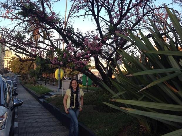 Caroline em frente da cerejeira florida (Foto: Caroline Rosa Della Nina/arquivo pessoal)