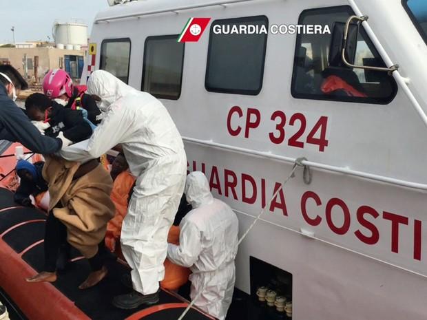 Imagem de vídeo cedido pela Guarda Costeira da Itália mostra guardas socorrendo migrantes que foram resgatados em Lampedusa, no sábado (30) (Foto: HO/AFP Guardia Costiera/AFP)