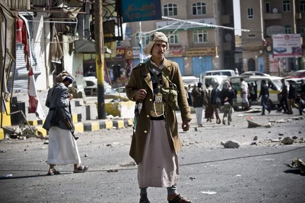 Miliciano xiita é visto patrulhando rua que dá acesso ao palácio presidencial em Sanaa, no Iêmen, nesta terça-feira (20) (Foto: Hani Mohammed/AP)