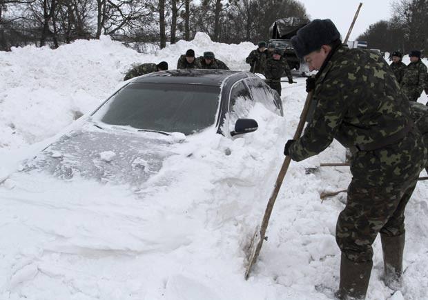 Militares desenterram carro coberto por neve nesta segunda-feira (17) na cidade ucraniana de Brody (Foto: Reuters)