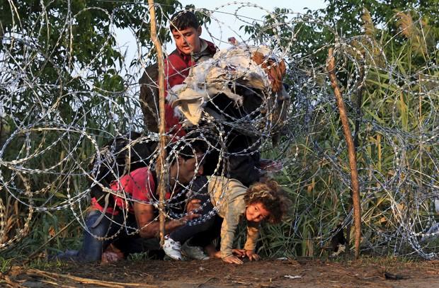 Migrantes sírios atravessam cerca na cidade húngara Roszke nesta quinta-feira (27) (Foto: Bernadett Szabo/ Reuters)