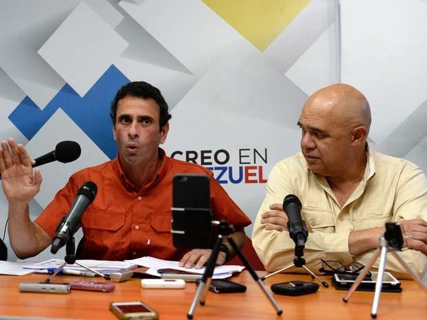 O governador de Miranda e oposito venezuelano Henrique Capriles fala ao lado do presidente da coalizão de oposição MUD,  Jesus Torrealba, durante coletiva de imprensa nesta sexta-feira (13) em Caracas (Foto: AFP PHOTO/FEDERICO PARRA)