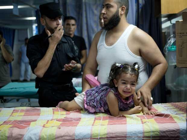 Palestino leva sua filha a um hospital após ataque aéreo israelense na cidade de Gaza. (Foto: Mohammed Abed / AFP Photo)