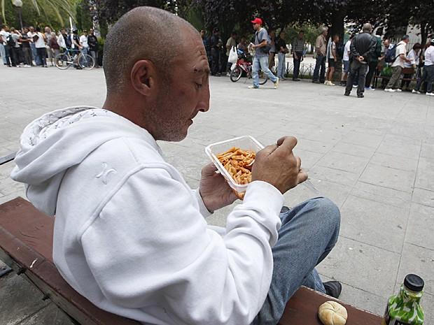 Espanhol come macarrão distribuído por voluntários em Valência (Foto: Heino Kalis/Reuters)