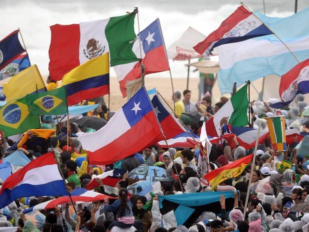 Várias bandeiras nacionais são carregadas no primeiro dia da JMJ em Copacabana (Foto: Tasso Marcelo/AFP)