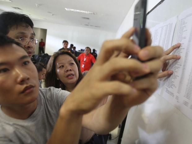 Parentes e amigos dos passageiros do voo QZ-8501 da AirAsia conferem lista de ocupantes do Airbus da AirAsia divulgada no centro de crise montado no Aeroporto Internacional Juanda, na Indonésia (Foto: Trisnadi/AP)
