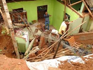 Moradores trabalham em casa destruída por queda de barreira, no distrito de Quatituba. (Foto: Leandro Santos Campos/Defesa Civil)