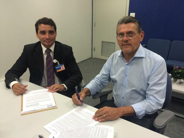 Bruno Silva (E), gerente regional da Caixa, assina convênio com Joel Martins, prefeito de Nova Serrana (Foto: PMNS/Divulgação)