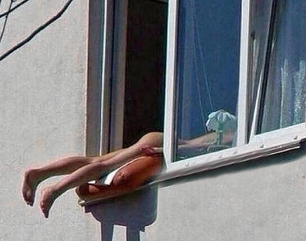 Mulher nua foi flagrada tomando banho de sol no parapeito de um prédio em Viena (Foto: Reprodução/YouTube/ DR. Alex)