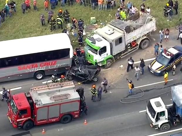 Carro preto ficou prensão entre ônibus e caminhão em acidente na Rodovia Fernão Dias (Foto: TV Globo/Reprodução)