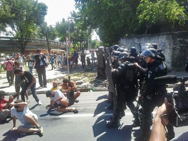 Policiais Militares do Batalhão de Choque jogam spray de pimenta em manifestantes sentados no chão (Foto: Katherine Coutinho/G1 PE)