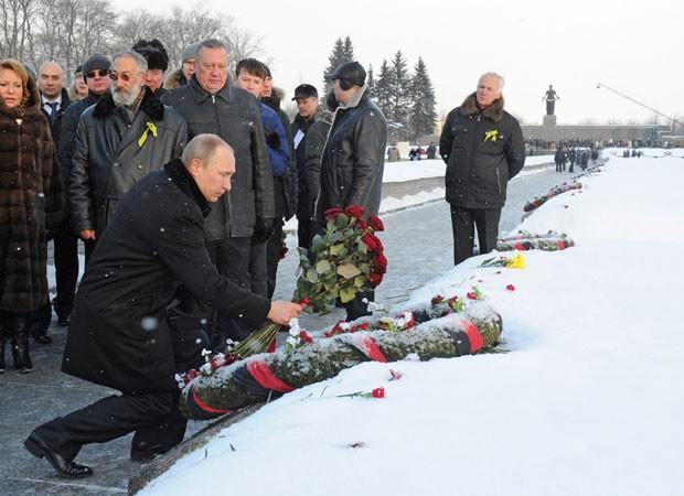 O presidente da Rússia, Vladimir Putin, deposita flores em uma das valas comuns  do cemitério de Piskaryovskoye, onde a maior parte das vítimas do cerco a Leningrado (hoje São Petersburgo) foi enterrada durante a Segunda Guerra Mundial (Foto: RIA Novosti Kremlin/Mikhail Klimentyev/Presidential Press Service/AP)